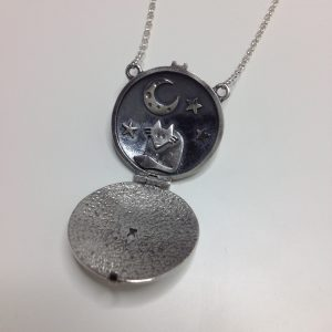 Our Midnight Fox locket shows a little fox sitting under the moon and stars.