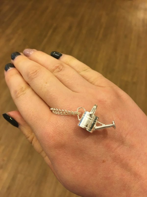 Silver Watering Can Pendant Shown on Hand