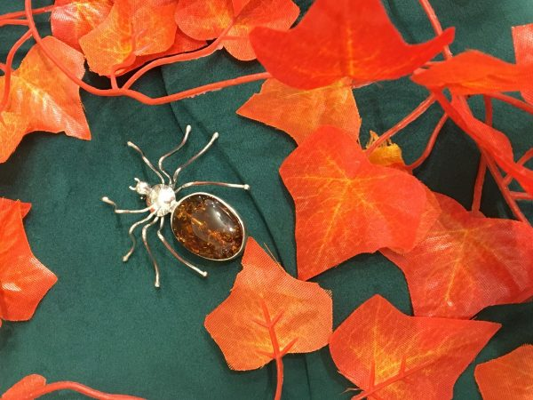 amber spider brooch in leaves