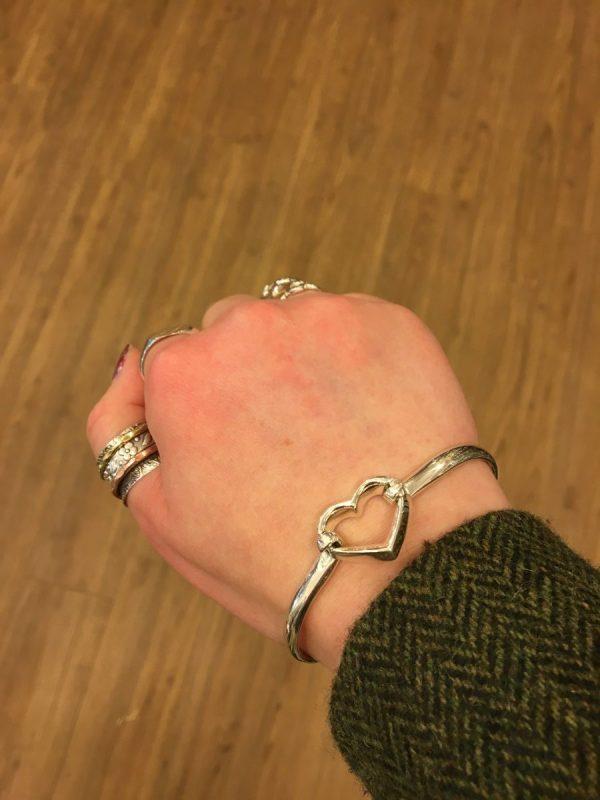 silver heart bangle on wrist