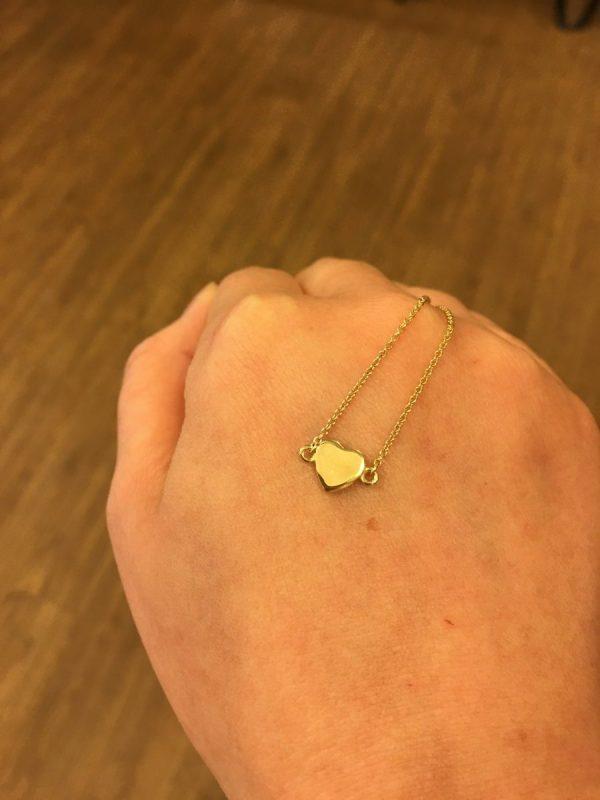 tiny gold heart pendant on hand