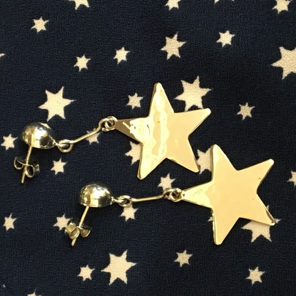 hammered star earrings on star background