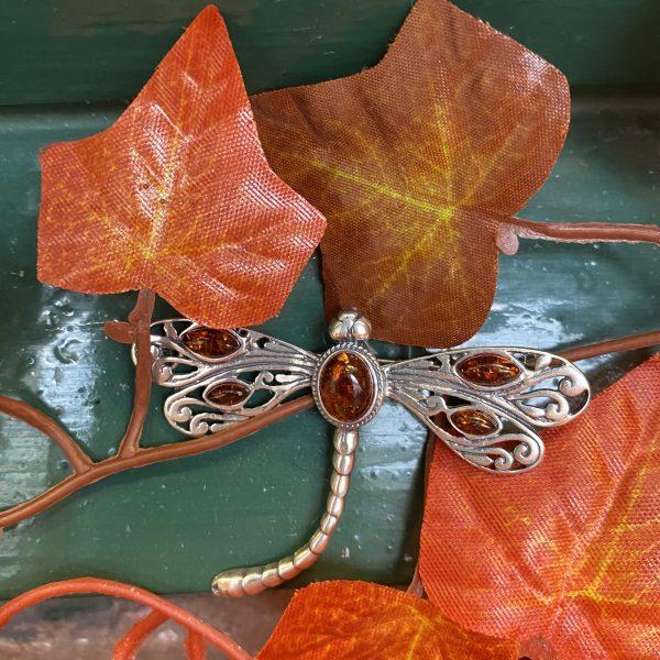 amber dragonfly brooch on green